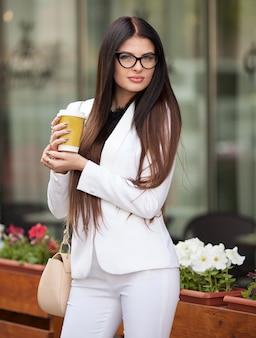 Retrato de empresaria profesional financiera sosteniendo en la mano una taza de café mientras camina a la convención financiera al centro de negocios.