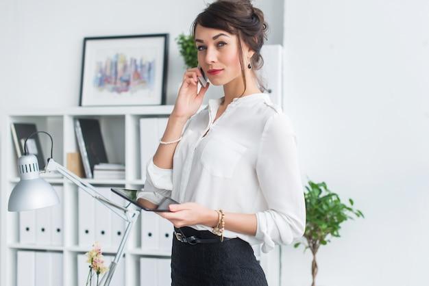 Retrato de una empresaria que tiene llamada de negocios, discutiendo detalles, planeando sus reuniones usando el diario y el teléfono celular.
