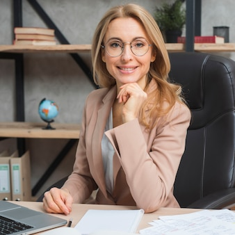 Retrato de una empresaria rubia joven confiada que se sienta en silla en el lugar de trabajo