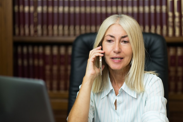Retrato de una empresaria senior utilizando un teléfono celular
