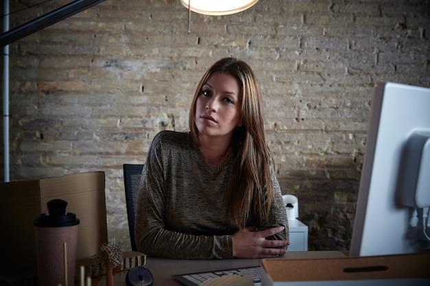 Retrato de la empresaria en la sentada interior de la oficina