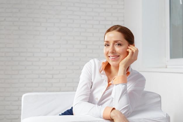 Retrato de la empresaria sentado en el sofá en la oficina moderna