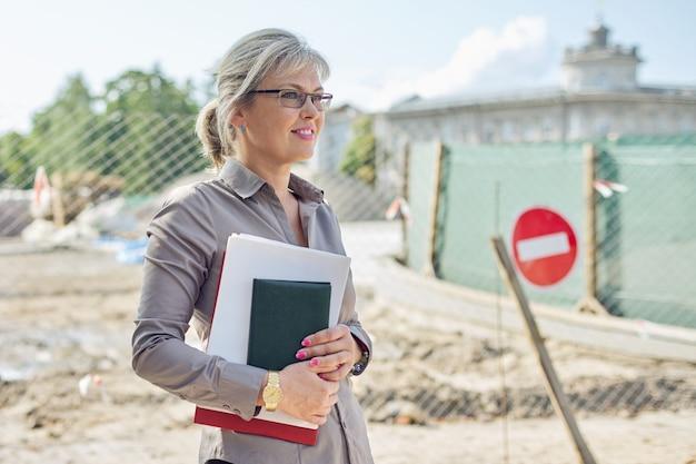 Retrato de empresaria en el sitio de construcción, reparación de carreteras