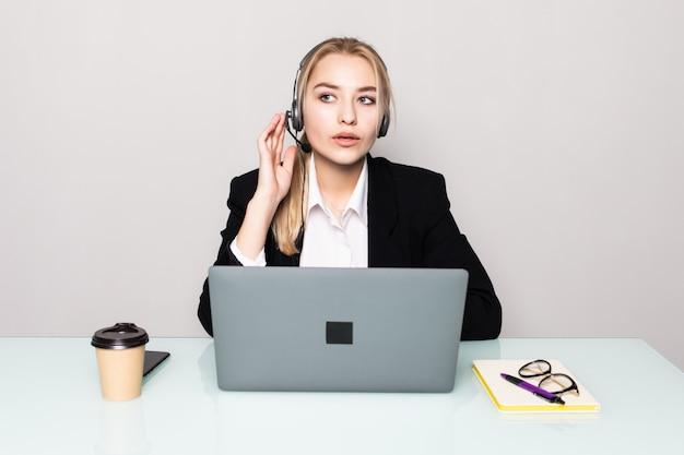 Retrato de una empresaria sonriente con un audífono trabajando en un call center en la oficina