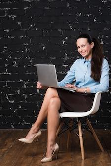 Retrato de una empresaria sonriente con portátil sentado
