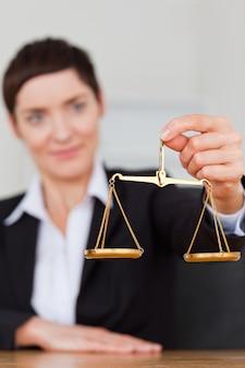 Retrato de una empresaria sosteniendo la escala de justicia
