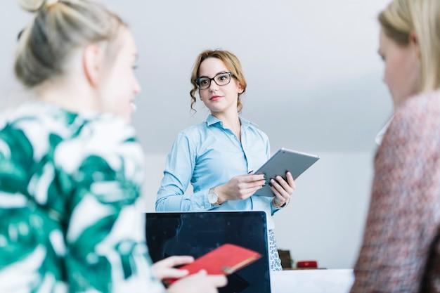 Retrato de empresaria sosteniendo tableta digital hablando con sus colegas