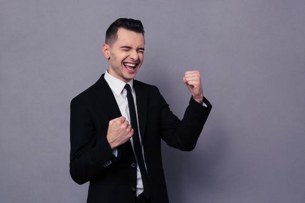 Retrato de un empresario alegre celebrando su éxito sobre la pared gris