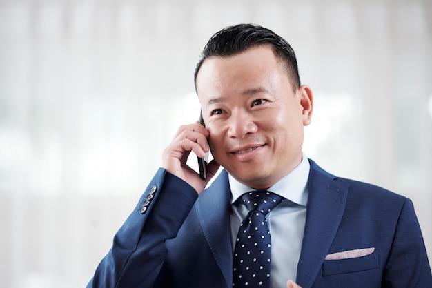 Retrato del empresario asiático que tiene una negociación telefónica con un socio comercial