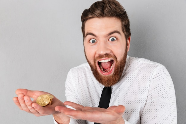Retrato de un empresario excitado mostrando bitcoins dorados