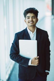 Retrato del empresario feliz indio usando la computadora portátil en la oficina