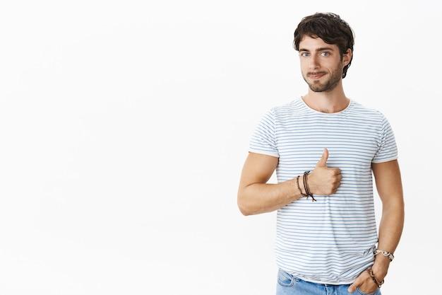 Retrato de empresario masculino satisfecho con encantadores ojos azules y barba sonriendo complacido mostrando los pulgares hacia arriba como mirando el buen trabajo del empleado siendo un jefe solidario