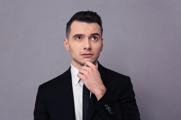 Retrato de un empresario pensativo mirando hacia arriba sobre la pared gris