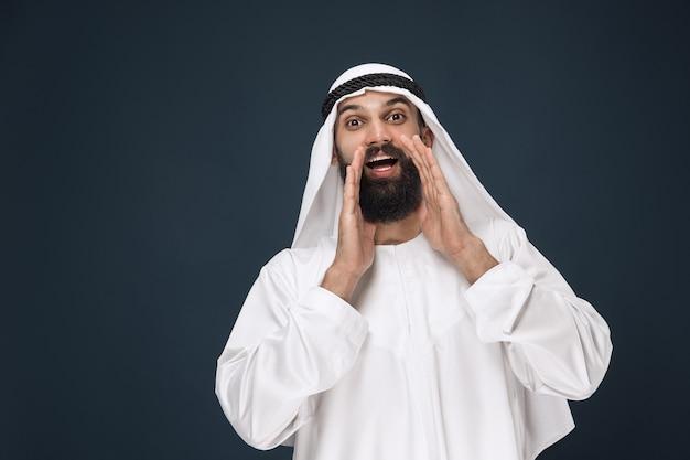 Retrato del empresario saudita árabe en la pared azul oscuro del estudio