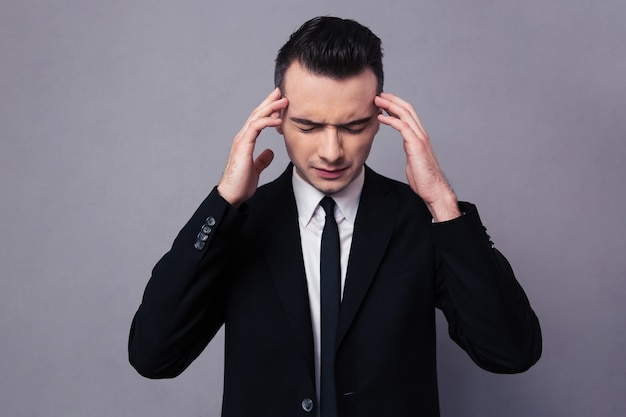 Retrato de un empresario seguro pensando sobre pared gris