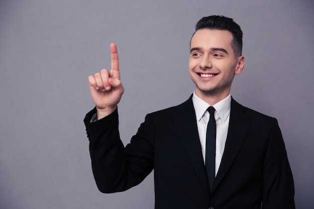 Retrato de un empresario sonriente apuntando con el dedo hacia arriba sobre la pared gris