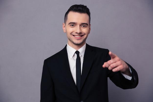 Retrato de un empresario sonriente dedo acusador sobre pared gris