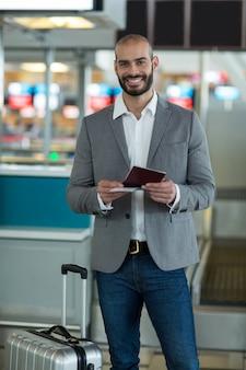 Retrato del empresario sonriente con equipaje comprobando su tarjeta de embarque
