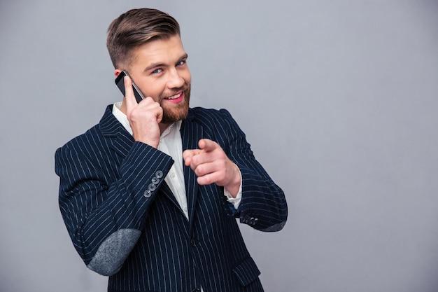 Retrato de un empresario sonriente hablando por teléfono y señalando con el dedo a la cámara sobre pared gris