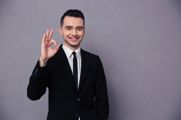 Retrato de un empresario sonriente mostrando ok firmar sobre pared gris