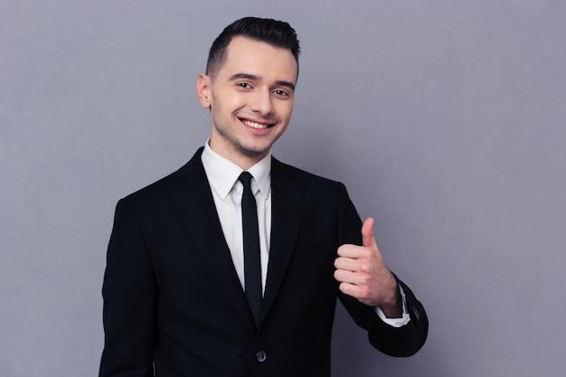 Retrato de un empresario sonriente mostrando el pulgar hacia arriba sobre la pared gris