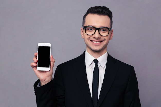 Retrato de un empresario sonriente shoing pantalla de smartphone en blanco sobre pared gris