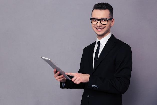Retrato de un empresario sonriente con tablet pc sobre pared gris