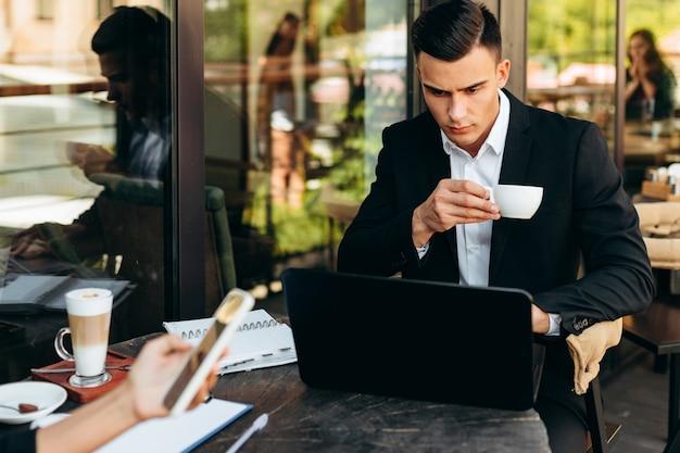 Retrato del empresario sosteniendo una taza de café y mirando la pantalla del portátil