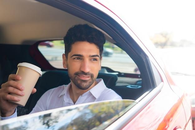 Retrato del empresario tomando café en su camino al trabajo en coche