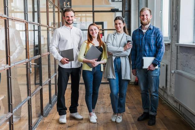 Retrato de los empresarios sonrientes que se colocan en oficina