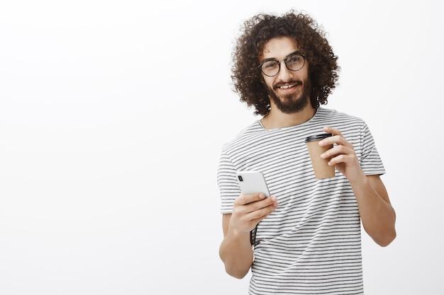 Retrato de encantador chico juguetón con barba y cabello rizado, tomando café y sosteniendo un teléfono inteligente, mirando con curiosidad