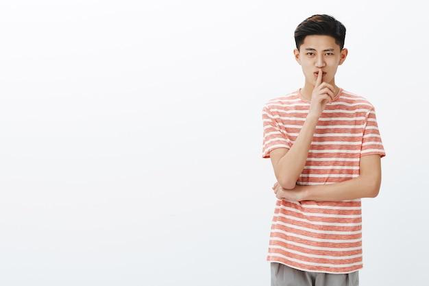 Retrato de encantador misterioso joven adolescente asiático con peinado corto mostrando gesto de silencio y sonriendo con sorpresa o compartiendo secreto