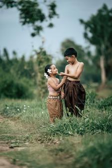 Retrato de un encantador niño asiático sin camisa y una niña en traje tradicional tailandés y poner una hermosa flor en su oreja, de pie de la mano y mirando al cielo con una sonrisa, espacio de copia