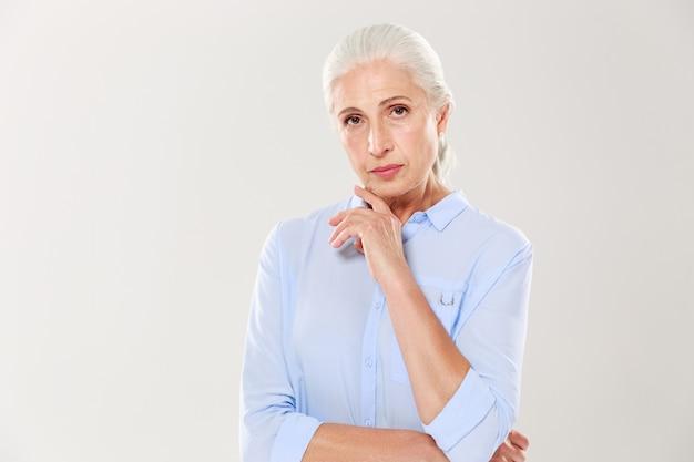 Retrato de encantadora anciana seria, en camisa azul, tocando su barbilla