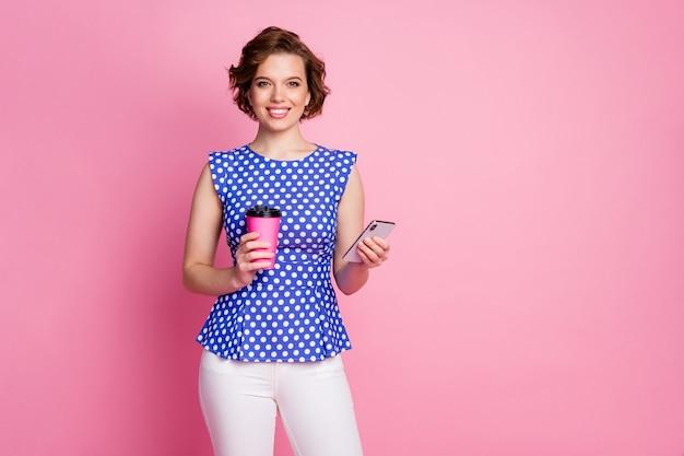 Retrato de encantadora chica alegre bebiendo café con leche mantenga teléfono