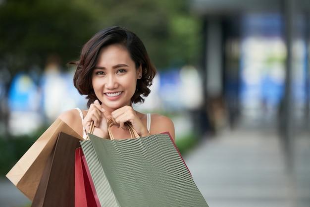 Retrato de encantadora chica compradora compulsiva de pie con una pila de bolsos de compras al aire libre