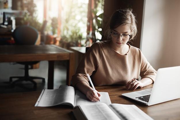 Retrato de encantadora estudiante caucásica enfocada en gafas, escribiendo con bolígrafo en el cuaderno, trabajando con el portátil, recopilando información de internet.
