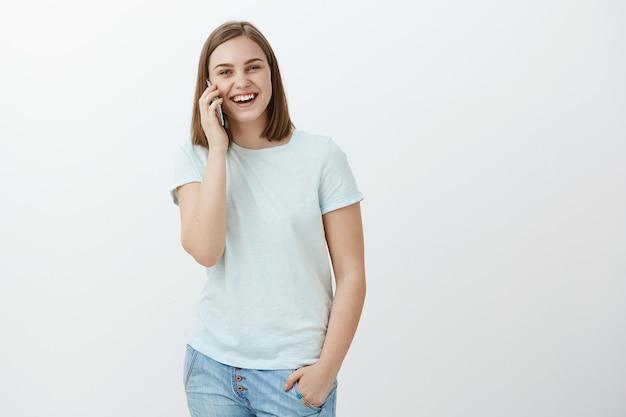 Retrato de encantadora mujer feliz y entretenida con smartphone cerca de la oreja llamando y hablando divertido sobre pared blanca