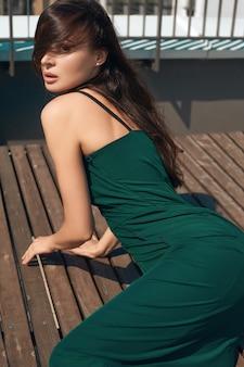 Retrato de una encantadora mujer morena brillante con un vestido esmeralda posando en la azotea de un edificio