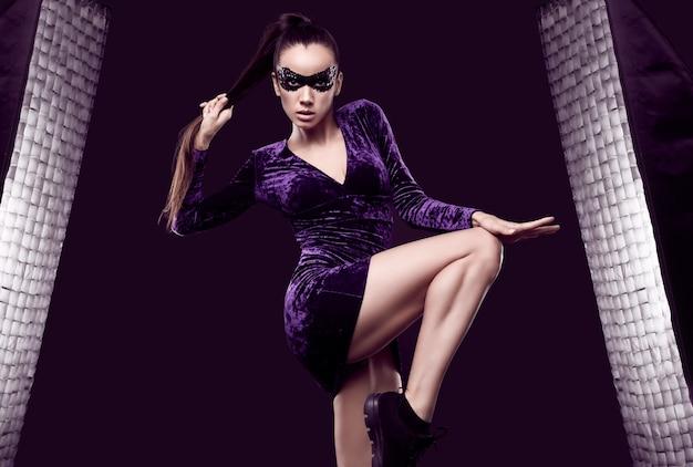 Retrato de encantadora mujer morena elegante en vestido púrpura hermoso y máscara de lentejuelas posando sobre fondo negro en estudio