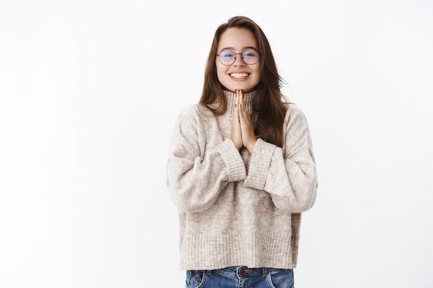 Retrato de encantadora niña coqueta tonta con gafas y un suéter tomados de la mano en rezar cerca del pecho y sonriendo ampliamente