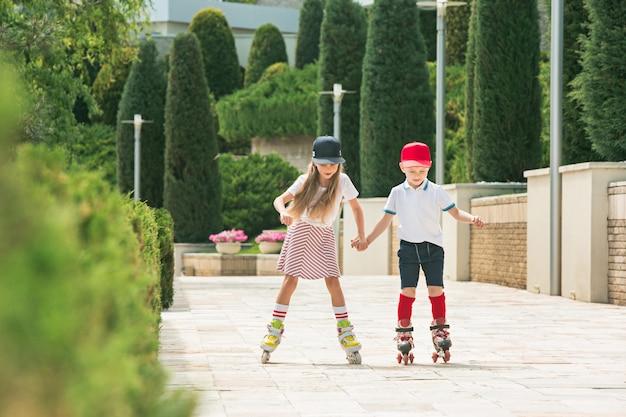 Retrato de una encantadora pareja de adolescentes patinando juntos sobre patines en el parque.