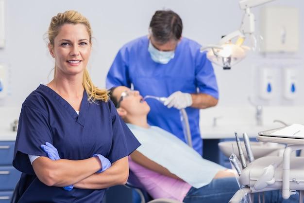 Retrato de una enfermera sonriente con los brazos cruzados y el dentista con el paciente detrás de él