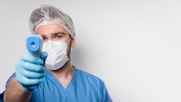 Retrato de enfermera sosteniendo termómetro infrarrojo