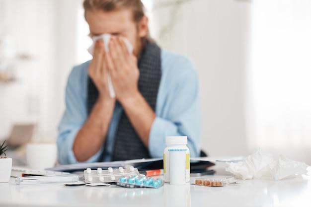 Retrato de enfermos, enfermos barbudos estornuda y tose, usa pañuelo, se frota la nariz. el hombre tiene goteo nasal, caugh, resfriado, se sienta en el lugar de trabajo, rodeado de píldoras, drogas y vitaminas.
