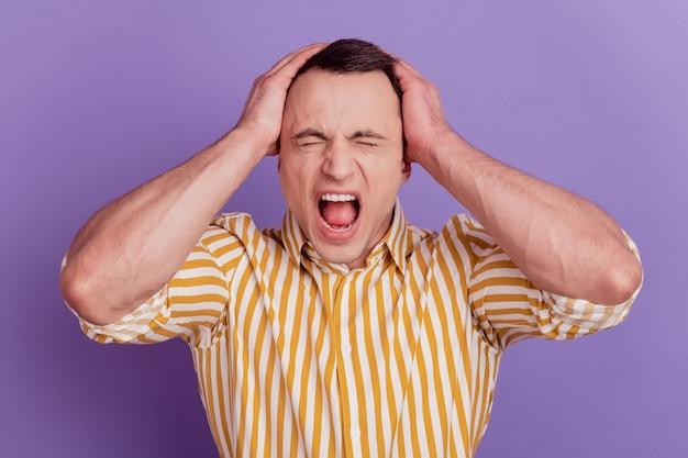 Retrato de enojado chico agresivo manos cabeza abierta grito de boca sobre fondo violeta