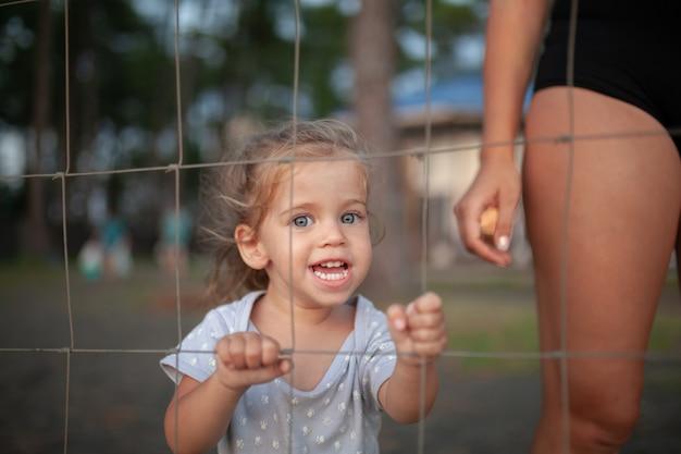 Retrato entonado de niña triste mira a través de la cerca de alambre