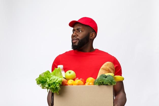 Retrato de entrega hombre afroamericano en camisa roja. el levantando cajas de comestibles pesadas