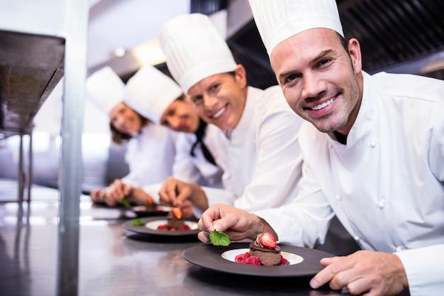 Retrato del equipo de chefs terminando platos de postre