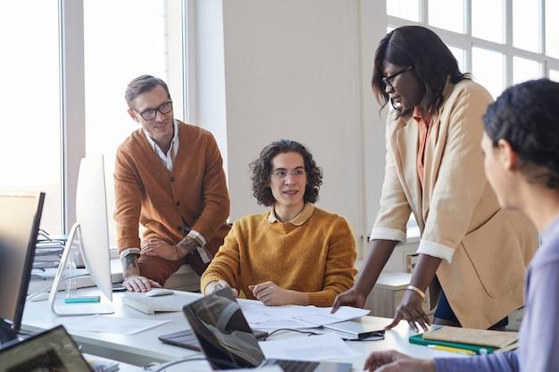 Retrato del equipo de desarrollo de software multiétnico discutiendo el proyecto mientras usa computadoras en la oficina moderna, espacio de copia